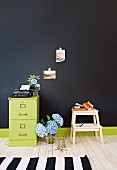 Antique typewriter on a metal cabinet, floral decoration and wooden stool in front of a black wall
