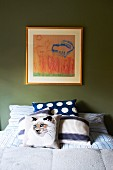 Cat motifs on scatter cushion and in framed picture on green bedroom wall
