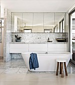 Spacious, bright gray and white bathroom with free standing bathtub and mirrored floating cabinets