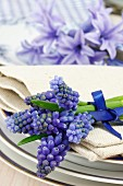 Place setting decoration with grape hyacinth (Muscari) on a linen serviette