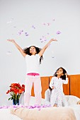 Sisters bouncing on bed & throwing feathers in the air