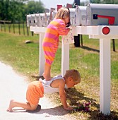Little girl standing on brother's back peering into post box