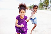 Two dark-skinned girls running along beach hand in hand