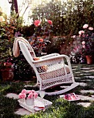 White, wicker rocking chair in romantic rose garden