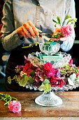 Hands of woman creating flower arrangement with roses on crystal fruit stand