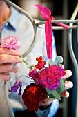 Hands of woman creating flower arrangement using sphere of oasis foam