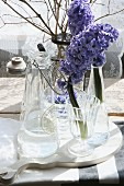 Blue hyacinths in glass vase on white wooden board on rustic table