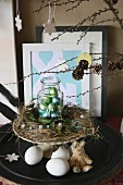 Easter arrangement; wreath of hay and jar of chocolate eggs on cake stand with egg shells and plush Easter bunny on table below
