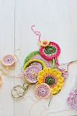 Crocheted coasters of various colours on white surface