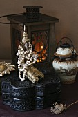 Bead necklace on Buddha figurine on carved, black wooden box and Chinese vase in front of lit candle lantern