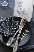 Place setting; napkin folded into lotus flower, tealight in translucent paper bag and letters on plate