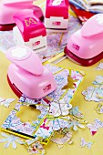 Pink punches and flower and butterfly shapes punched out of old maps