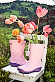 Tulips in pink wellingtons on garden chair