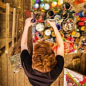 Birds-eye view of young artist working at table with pots of paint in artists' studio