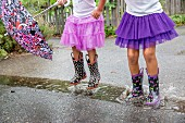 Two girls in purple tulle skirts and colourful wellington boots jumping in puddle