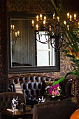 Detail of hotel restaurant with leather sofa, mirror on wall and chandelier