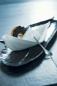 Napkin boat with spoon as rudder and round biscuit as decorative place setting on long, narrow plate