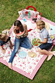Children eating picnic on floral picnic blanket