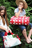 Children outdoors with picnic bag and rolled blanket with red and white polka dot pattern