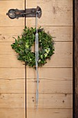 Rustic wooden door with wreath of mistletoe and Star-of-Bethlehem hanging from wrought iron latch