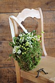 Romantic, bag-shaped arrangement of moss, mistletoe and Star-of-Bethlehem on wooden chair