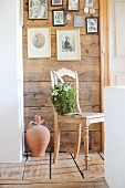 Romantic, bag-shaped arrangement of moss, mistletoe and Star-of-Bethlehem on wooden chair below gallery of photos on wooden wall