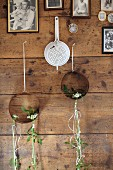 Vintage enamel sieve and rusty metal rings decorated with delicate arrangements of Star-of-Bethlehem hanging on rustic wooden wall