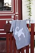 Graues Shirt mit selbstgenähtem Tiermotiv auf Holzzaun hängend