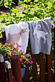 T-shirts with hand-sewn animal motifs hanging on garden fence