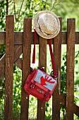 Strohhut & Umängetasche mit appliziertem rotem Hirschmotiv an Holzzaun hängend