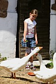 Child feeding geese in front of country house