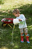 Child wearing wellingtons & hand-sewn top playing with bucket of water in garden
