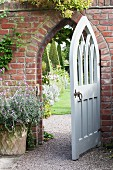 White, wooden, Gothic-style open garden gate in brick wall with view of topiary box trees beyond