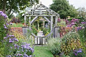 Blooming flower beds in garden with brick wall and wooden gate in front of traditional pergola in silvery wood