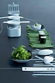 Gedeckter Tisch mit Sushi, Algensalat und Bohnen
