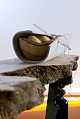 Stylised hunters' meal - wooden bowl of potatoes wrapped in felt mat on improvised, live-edge wooden table