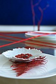 Asiatische Tischdeko: Blattförmiges Schälchen mit rotem Pfeffer auf rotgefäbtem Farnblatt und weißem Teller, roter Wollfaden umwickelt Tisch