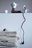 Espresso pot on hotplate on wall behind retro desk bell on stack of magazines