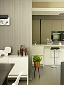 Detail of dining area with white sideboard against wooden wall varnished pale grey; modern, white fitted kitchen with bar stools at counter in background