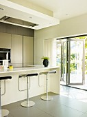 Contemporary, open-plan kitchen with grey tiles floor & bar stools at breakfast bar; open folding doors with view of terrace to one side