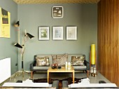 Lounge area with grey-painted walls in modern retro look with small coffee table, animal-skin rug & sofa amongst fifties-style standard lamps