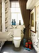 Grossformatige Fliesen mit floralem Muster in Bad mit drapiertem Fenstervorhang & Retro-Vasensammlung neben Toilette