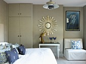 Bedroom in shades of grey & blue with bedroom, floor-to-ceiling wardrobe, mirror with sunburst frame, side table and easy chair in niche