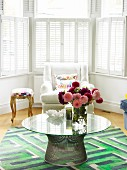 60s table on rug with geometric pattern and armchair in bay window with interior shutters
