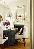 Dining area with grey damask tablecloth on round table and designer arc lamp; vintage mirror above open fireplace in background