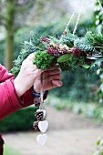 Hand-crafting a winter wreath with bird feeders