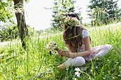 Girl sitting in meadow wearing wreath of flowers & holding bouquet of ox-eye daises