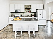 Bar stools at central island with stainless steel worksurface in white, open-plan kitchen