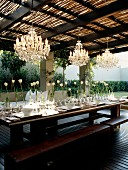 Outdoor table with integrated benches on roofed wooden terrace; table festively set with row of white tulips below chandeliers