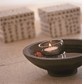 Tealight holder in brown ceramic bowl of water